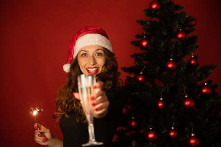 Beautiful long-hair brunette girl in Santa Claus hat distant celebrates New Year with loved ones online with Burning sparklers and flute of champagne in hands Christmas tree on studio red backdrop