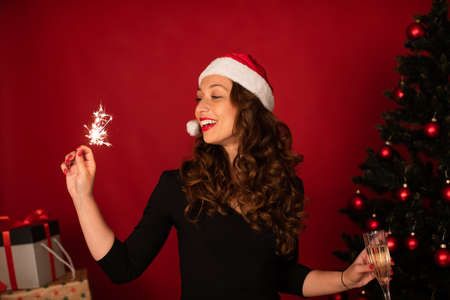 Beautiful long-hair brunette girl in Santa Claus hat dancing with Burning sparklers and flute of champagne in hands celebrating Christmas and New Year alone. self-gifter at Christmas tree concept