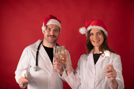 Two smiling doctors in Santa Claus hats cheering with champagne flutes and Burning sparklers on red studio background. Merry Christmas and Happy New Year for healthcare professionals Archivio Fotografico