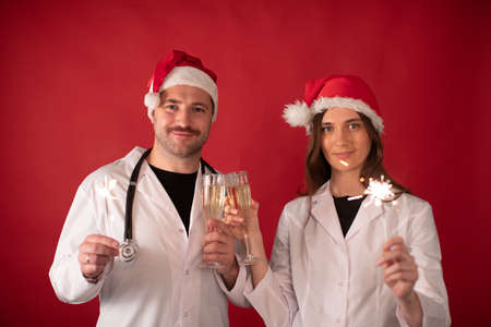 Two smiling doctors in Santa Claus hats cheering with champagne flutes and Burning sparklers looking at camera on red studio. Merry Christmas and Happy New Year for healthcare professionals