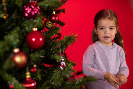 Smiling happy child baby girl posing at Christmas tree on red studio Xmas background. Children and Christmas concept. preparation for holidays. Merry Christmas! Happy New Year! Archivio Fotografico