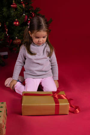 thoughtful child toddler girl looking at gift box on background of Christmas tree. red Xmas studio copy space. Christmas gift ideas. Waiting for miracle concept. Merry Christmas! Long-distance gifting