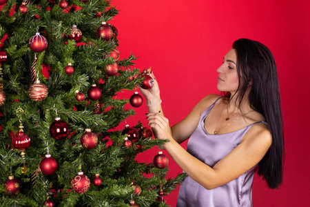 long-hair brunette girl in dress with open shoulders dresses up Christmas tree on studio red backdrop. Christmas vacation in quarantine alone. decorate Christmas tree yourself
