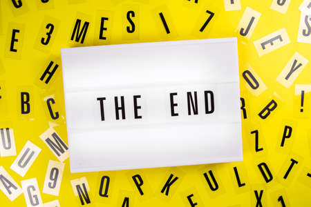 The End message on lightbox on scattered letters background of plastic alphabet. Project end, finish, end expectations, death concept concept