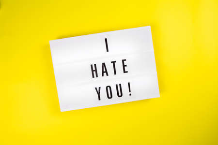 I Hate You! message on lightbox on yellow background isolated. Top view, flat lay. Recognition of hatred, racial, gender, social discord, anger, desire to kill, divorce, ruined human relations concept Zdjęcie Seryjne