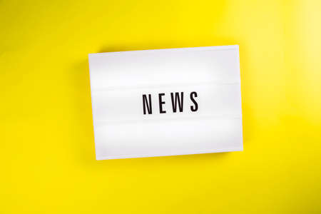 News word on lightbox on yellow background isolated. Top view, flat lay. world imbued with information, informational reasons, daily news, messages, informational noise concept