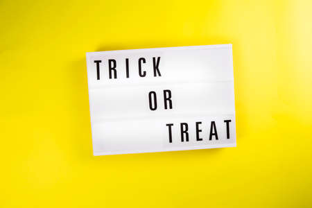 Trick or Treat message on lightbox on yellow background isolated. Holiday greeting card, party flyer, invitation concept concept