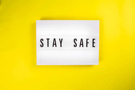Stay Safe message on lightbox yellow background isolated. Top view, flat lay. devices. Social distancing. Protection against pandemics. Safety rules, insurance policy, insurance services