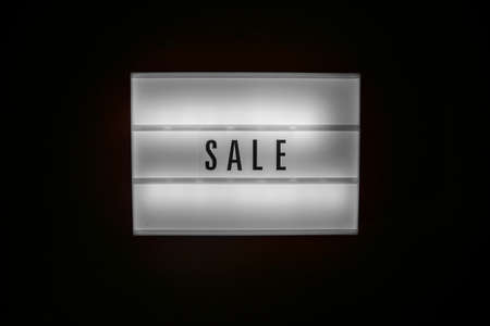 Sale word on Illuminated lightbox in dark. Concept Black friday, season sales time. Sales, special offers, discounts, elimination of last years collection concept