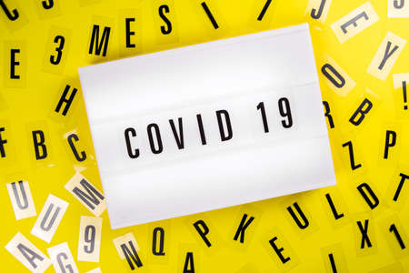 Lightbox with text COVID 19 on yellow background with black letters randomly scattered. Concept of coronavirus pandemic, worldwide lockdown, medical research news, vaccination, analytics, statistics Zdjęcie Seryjne