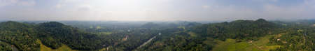 Panorama of hilly terrain with river in central Sri Lanka air view. Tropical greenery, picturesque hills, agricultural fields under blue sky