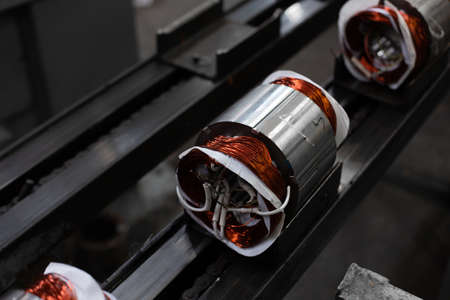 electric motors manufacture in industrial company - stators on assembly line of Semi-automated manual production. 20th century technology, obsolete factory processes concept.