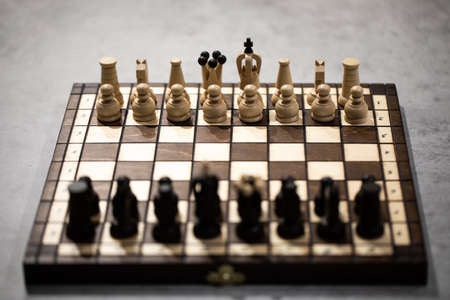 Wooden Chess pieces on board, arranged in incorrect initial position selective focus backlit. White king is at wrong Chessboard square. Royal mistake, transfer of powers, secret court intrigues