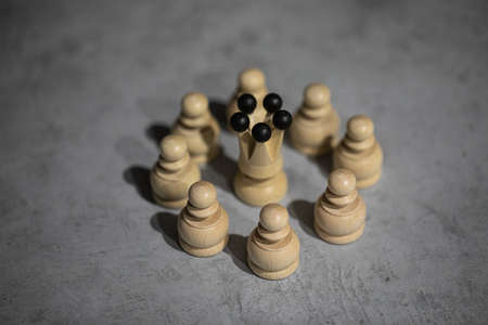 white queen wooden chess piece surrounded by white pawns standing on gray table copy space. Women Teamwork, close-knit teams, vertical social ties. Leader and subordinates, leadership positions