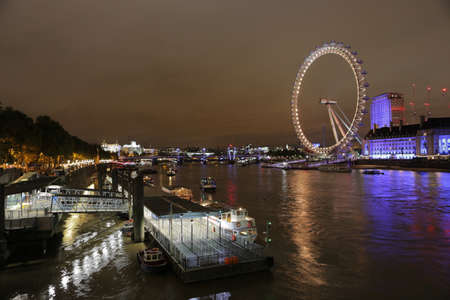 London, UK, 2.09.2016 - Ferry boats on River Thames at night in front of London Eye (Millennium Wheel), famous ferris observation wheel on South Bank of River Thames. piers and illuminated promenade Publikacyjne