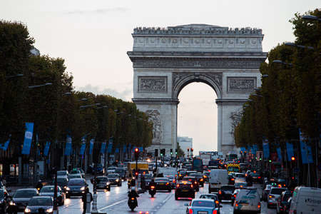 Paris, France, 1.11.2019 - evening car Traffic jam on Champs Elysees with view of Arc de Triomphe. Travel Greeting Card from Paris with love. Monument commemorating victories of Napoleons army