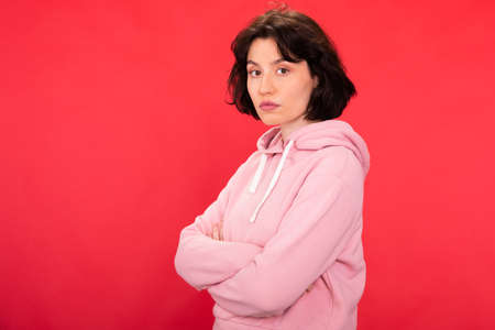 Young serious woman in trendy hipster hoodie poses with crossed arms, copy space