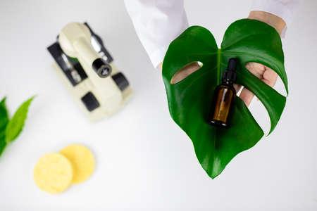 Face serum on green leaf on white lab background, plant-based cosmetics concept Zdjęcie Seryjne