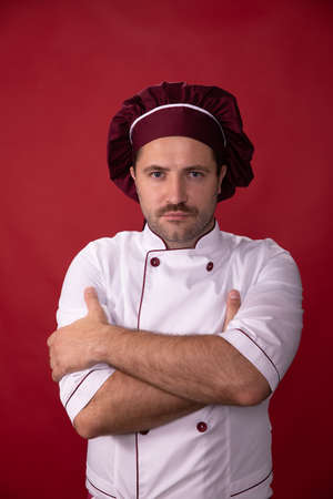 Portrait of handsome chef in uniform looks at camera on red background Zdjęcie Seryjne
