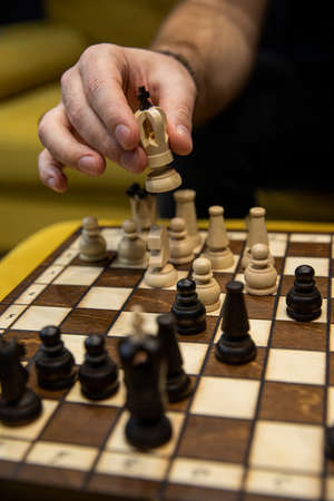 Man taking next step on chess game. Human hand moving wooden white chess king Zdjęcie Seryjne