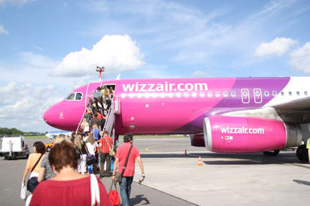 Vilnius, Lietuva, 1.09.2020 - Passengers board low cost airline Wizz Air Airbus A320 aircraft at Vilnius Airport. Tourists go up stairs near cockpit