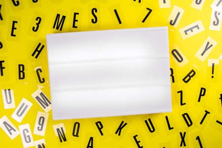Empty blank lightbox with copy text space for message on yellow background with black alphabet letters randomly scattered. Concept of news, advertising, education, literacy, announcement, banner Zdjęcie Seryjne