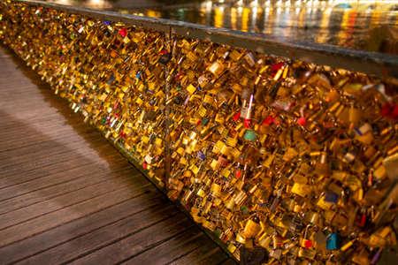 Paris, France, 1.11.2019 - Thousands golden Love locks on Pedestrian bridge Ponts des Arts, symbol of eternal love. Paris - city of lovers, romantic night walk concept. River Seine reflects lights Publikacyjne