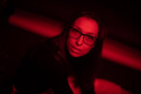 Portrait of sensual beautiful woman in glasses posing in red light dark studio