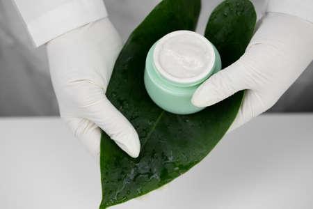 Close-up hands in medical gloves hold cream jar on green leaf, white background Zdjęcie Seryjne