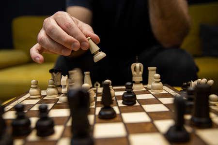 Hand taking next step on chess game. Human hand moving wooden dark bishop piece
