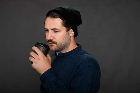 Young hipster guy in knitted hat holding coffee cup drinking hot drinks on dark background. Concept of enjoy break time, pause, leisure, freelancer, male student, tasty drinks, cafe, coffee shop