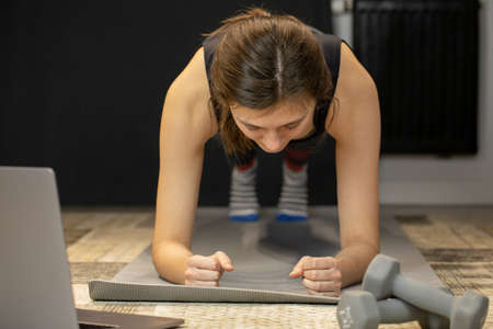 Young woman does abs exercise, enjoys bodybuilding training stands in plank Zdjęcie Seryjne