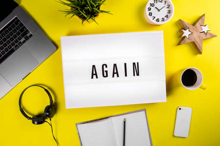 Lightbox with text message AGAIN on yellow background with laptop, smartphone, headphones, clock, notes. Concept of office workspace, business deadline, time to study, education, repetition learning