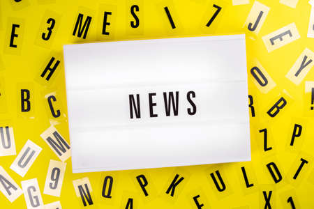 Lightbox with text message NEWS on yellow background with black letters randomly scattered. Concept of digital media, journalism, online tv announcement, information report, good and fake news, facts