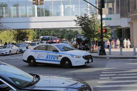 New York City, NY, USA 2.09.2020 - NYPD car at intersection of South End Avenue and Liberty Street downtown of Manhattan at summer day. police car with flashing lights rushes. serve and protect Publikacyjne