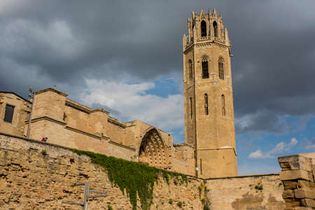 Lleida, Spain, May 1, 2020 - tower and fortress wall of La Seu Vella former Roman Catholic cathedral church under thunderclouds. Symbol of Reconquista, historical struggle between Moors and Christians