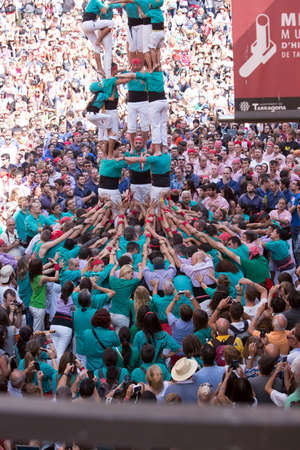 Tarragona, Spain, September 19, 2019 - Helmeted little Girl Climbing to Top of Human castells Tower. Childlike courage, emancipation concept. crowd of tourists watch erection of Castells human tower
