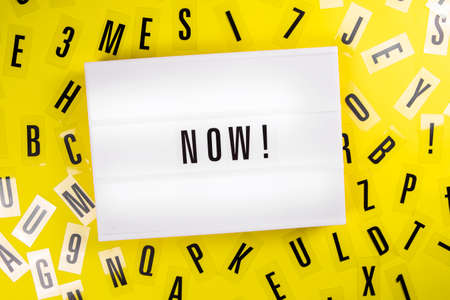Lightbox with text NOW on yellow background with black letters randomly scattered. Concept of motivation, hurry up sale announcement, start, buy now, register, join, in stock, actual info trends Foto de archivo
