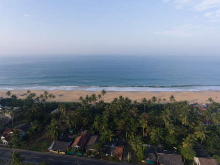 Hikkaduwa, Sri Lanka, 1.12.2020 - Amazing aerial view of Indian Ocean and beaches, cottages surrounded by tropical greenery and palm trees