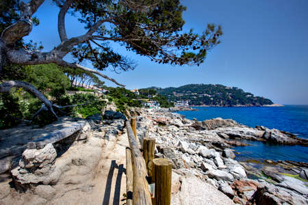 Calella de Palafrugell, Spain, May 1, 2020 - idyllic view of Costa Brava. Pine trees, rocks and sea - typical postcard views of Mediterranean coast of Catalonia. hiking trail along sea, hiking route Publikacyjne