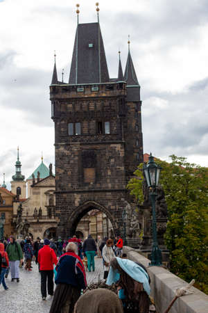 Prague, Czech Republic, 2.09.2020 - Old Tower of Charles Bridge, actors on filming historical movie on foreground. Tours of Old Prague, travel concept, heritage of medieval Europe