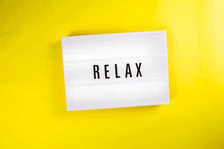 Lightbox with text message RELAX isolated on yellow background. Concept of chill, coffee break, rest, vacation, holiday, retreat, freelance remote work, summer, stress, relaxing, meditating, recharge Foto de archivo