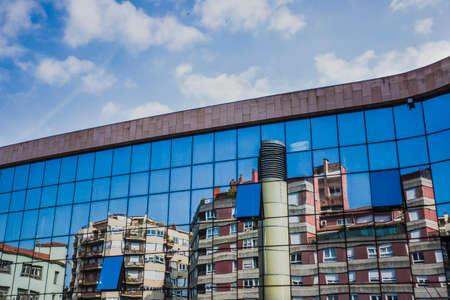Girona, Spain, May 1, 2020 - Gironas residential blocks are reflected in glass of modern building. Concept of old and new architecture, copy space on blue sky. diagonal line between sky and city