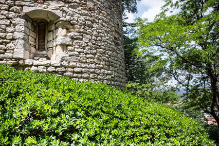 Girona, Spain, May 1, 2020 - medieval tower made of stone and covered with green vegetation