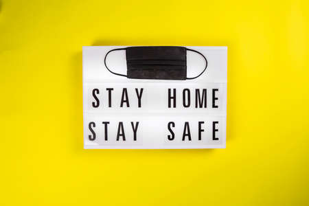 Lightbox with message STAY HOME STAY SAFE isolated on yellow background with black protective surgery mask. Foto de archivo