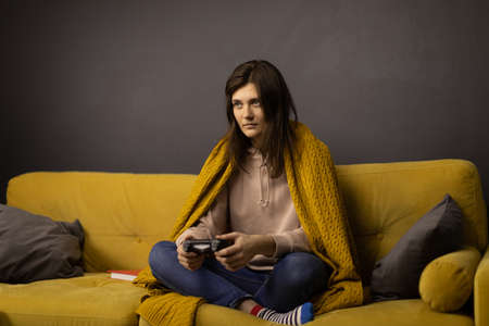 Attractive long-haired girl Playing Videogame alone sitting on comfy yellow sofa Stock Photo