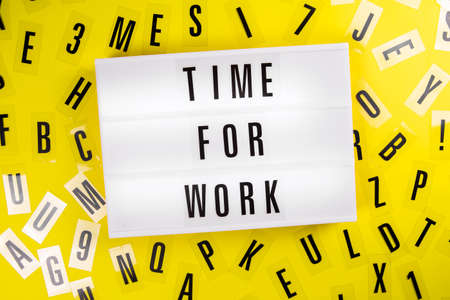 Lightbox with message TIME FOR WORK on yellow background with black letters randomly scattered. Concept of time management, deadline, overtime work, productivity, break, workaholic schedule, career