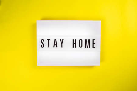 Lightbox with text message STAY HOME isolated on yellow background.