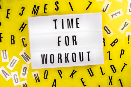 Lightbox with text TIME FOR WORKOUT on yellow background with black letters randomly scattered. Concept of everyday training, keep-fit, physical exercise session, health care, active lifestyle