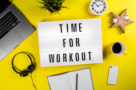 Lightbox with text TIME FOR WORKOUT on yellow background with laptop, smartphone, headphones and notes. Concept of change of scenery of office workspace, keep-fit, physical exercise session, training